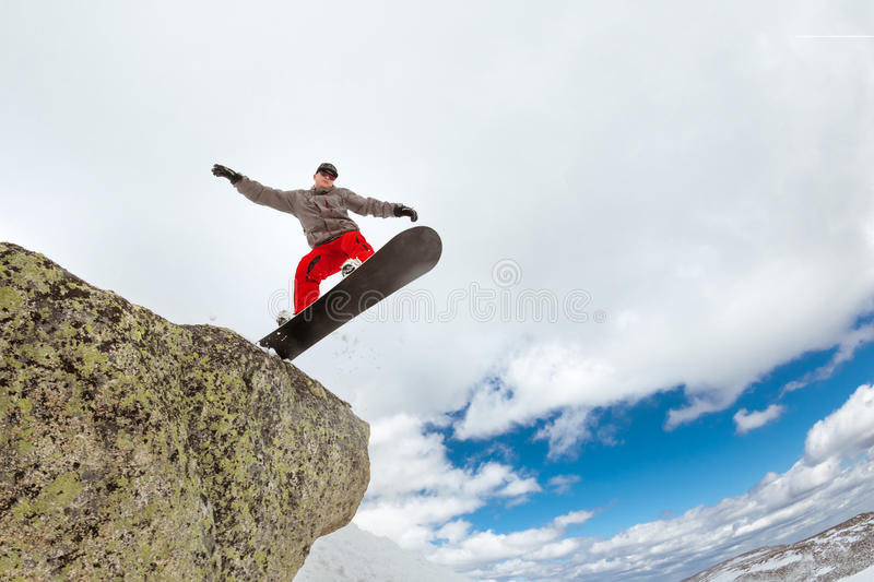 Snowboarder jumps from big rock stock photo