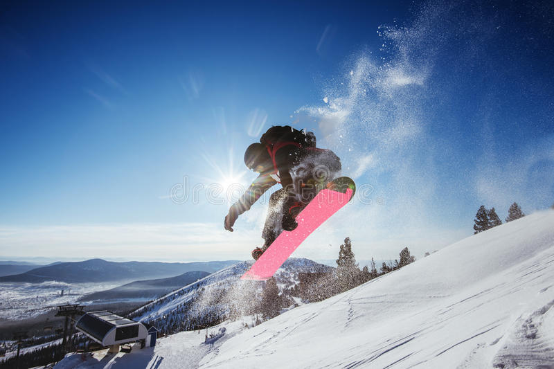 Snowboarder jumps on blue sky backdrop in mountains trick stock image