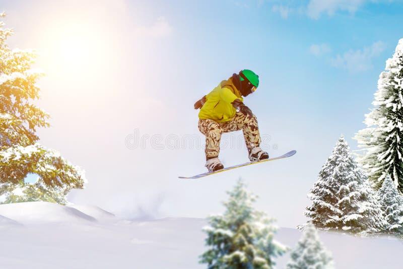 Snowboarder jumps in forest. Freeride snowboarding in ski resort stock image
