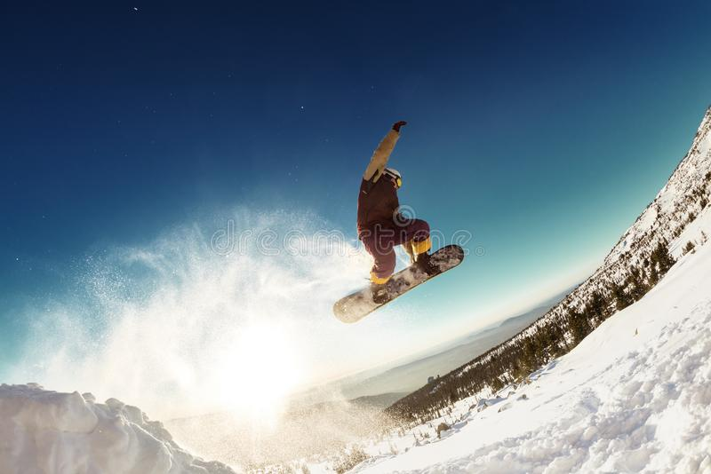 Snowboarder makes long jump from springboard royalty free stock images