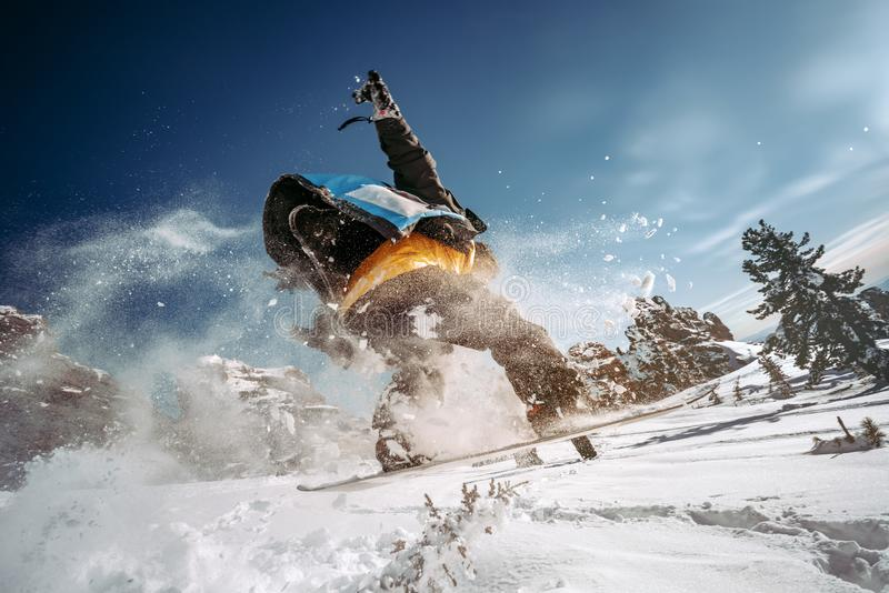 Snowboarder jumps from a springboard with tail of snow powder royalty free stock images