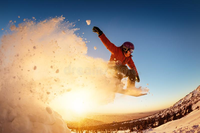 Snowboarder jumps sunset with snow dust stock photos