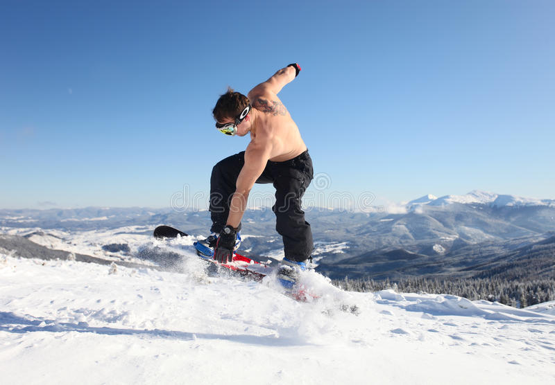 Snowboarder jumps up on the mountain top royalty free stock image