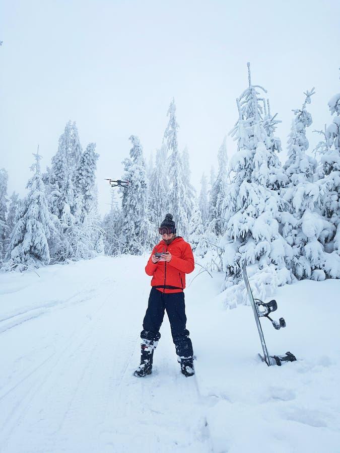 Snowboarder kontroluje trutnia podczas przerwy w łyżwiarstwie zdjęcie stock