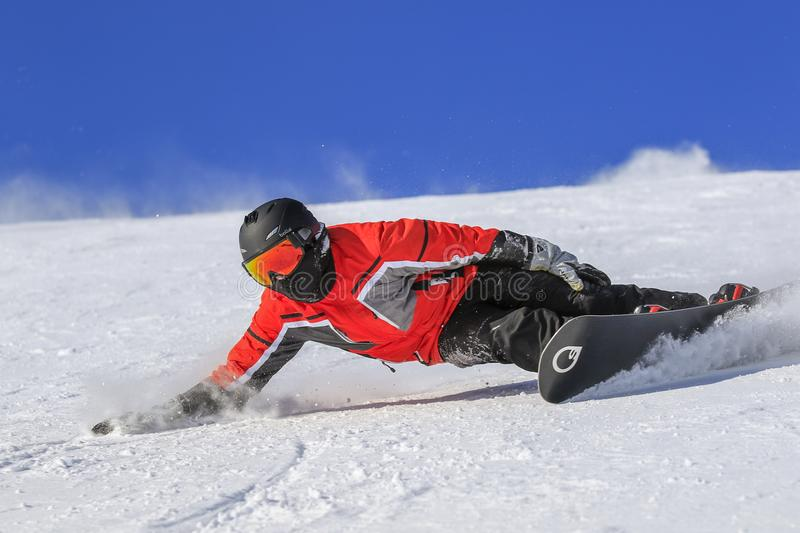 Snowboarder level pro near o the ice. ENCAMP - ANDORRA - JANUARY - 25 - 2017 snowboarder level pro dressed in red throws snow in an extreme move, on a sunny stock photography