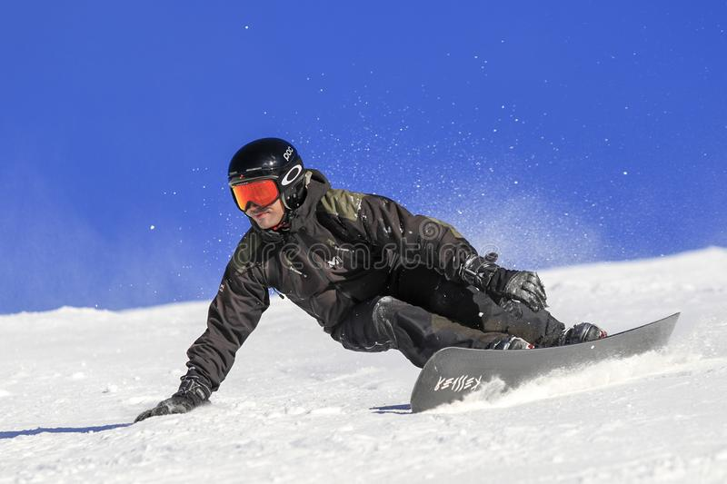 Snowboarder level pro, technique and balance. ENCAMP - ANDORRA - DECEMBER - 12 - 2016 snowboarder level pro going fast on the ski slope on a sunny and snowy day stock image