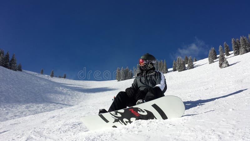 Snowboarder mâle glissant en bas de la montagne images stock