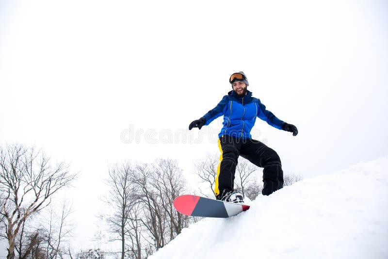 Snowboarder masculino na inclinação no recurso do inverno imagem de stock