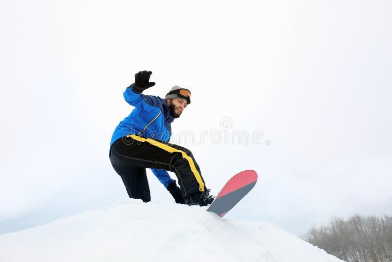 Snowboarder masculino na inclinação no recurso do inverno foto de stock