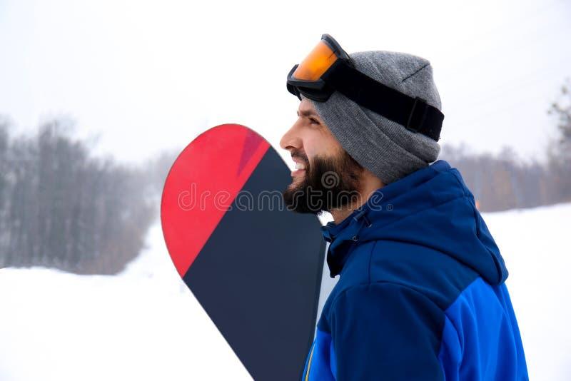 Snowboarder masculino na inclinação no recurso do inverno fotografia de stock