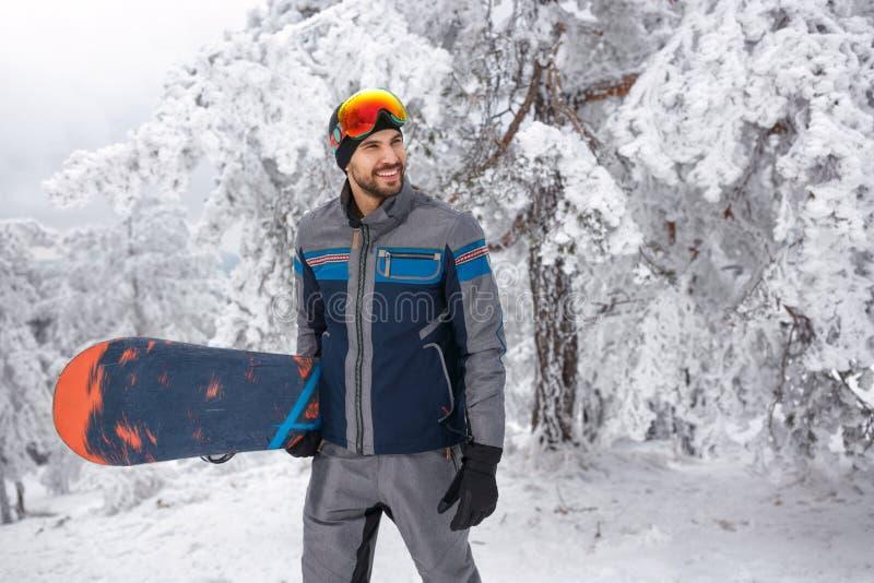 Snowboarder masculino novo com o snowboard no feriado de inverno no m fotografia de stock royalty free
