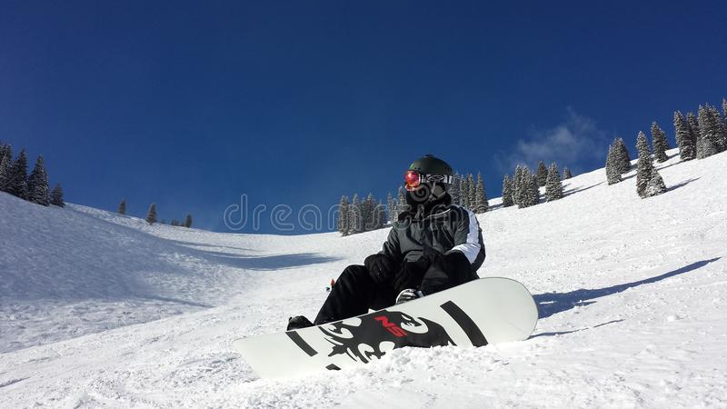 Snowboarder masculino que desliza abaixo da montanha imagens de stock