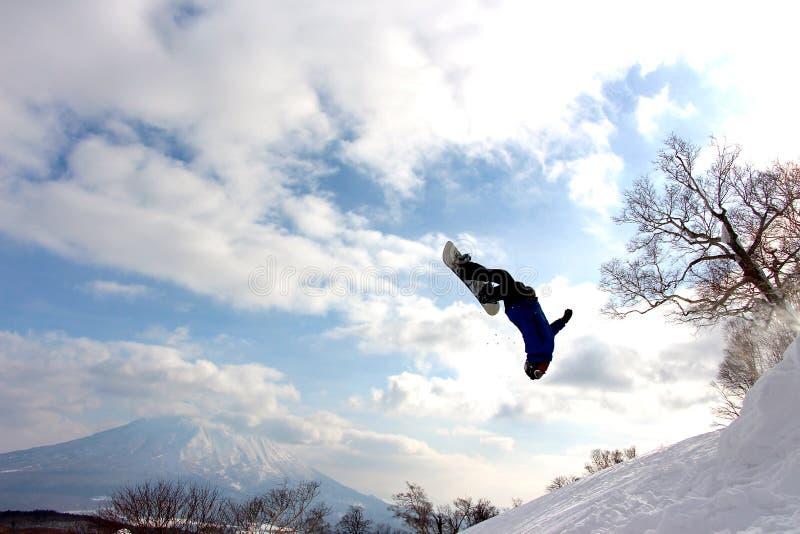 Snowboarder medio backflip bij hanazono backcountry sprong stock fotografie