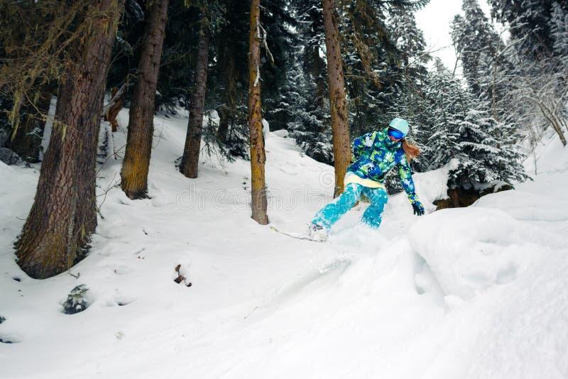 Snowboarder met speciaal materiaal berijdt en springt zeer snel in het bergbos stock foto's