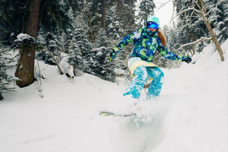 Snowboarder met speciaal materiaal berijdt en springt zeer snel in het bergbos stock afbeelding