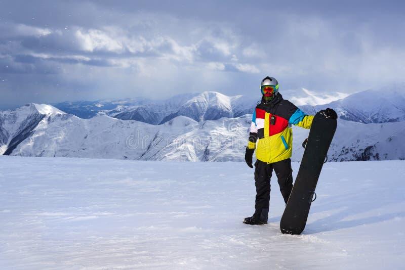 Snowboarder mienia snowboard w ręce na tle góry zdjęcia royalty free