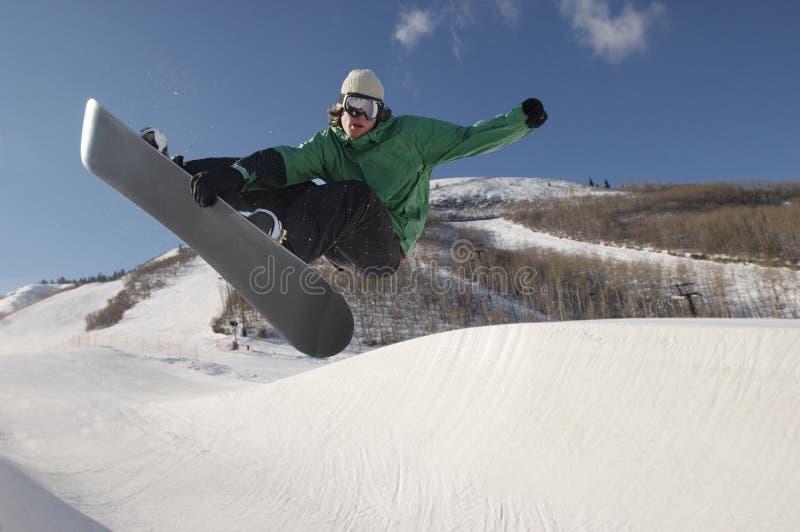 Snowboarder novo que executa conluios no monte nevado foto de stock royalty free