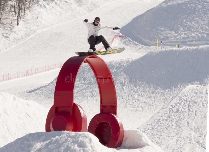 Snowboarder novo que faz truques jibbing fotos de stock