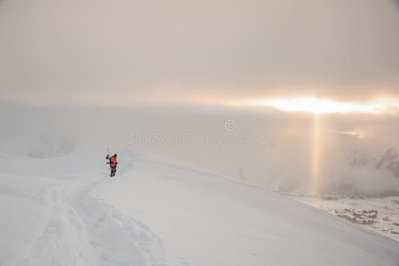 Snowboarder op de schitterende de winterzonsondergang in bergen Gudauri, Georgië stock afbeelding