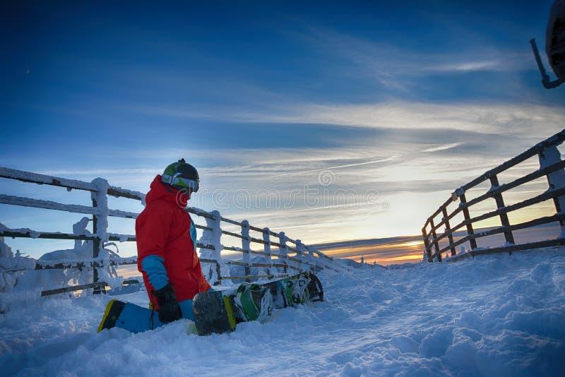 Snowboarder på berget i aftonen på solnedgången royaltyfri fotografi