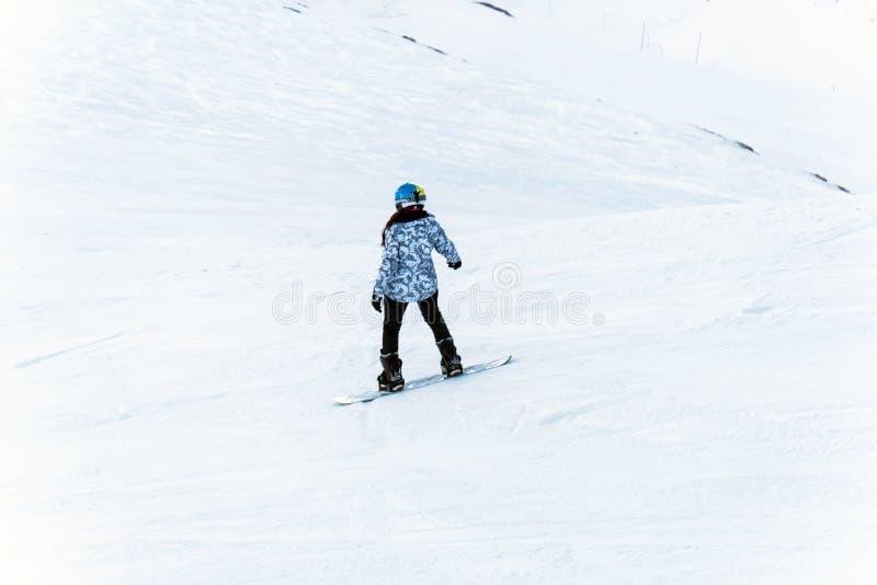 Snowboarder para baixo na inclinação nevado da fora-pista no inverno da luz da noite fotos de stock royalty free