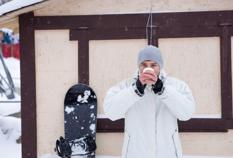 Snowboarder que bebe de la taza en la estación de esquí imagen de archivo