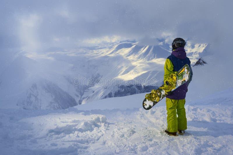 Snowboarder que coloca y que mira las montañas en tiempo nevoso imagen de archivo libre de regalías