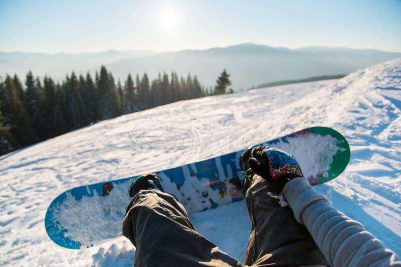 Snowboarder que descansa en las montañas foto de archivo libre de regalías