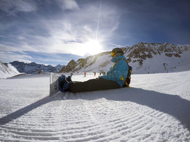 Snowboarder que descansa na inclinação - cena dos esportes de inverno Mountain View bonito fotografia de stock royalty free