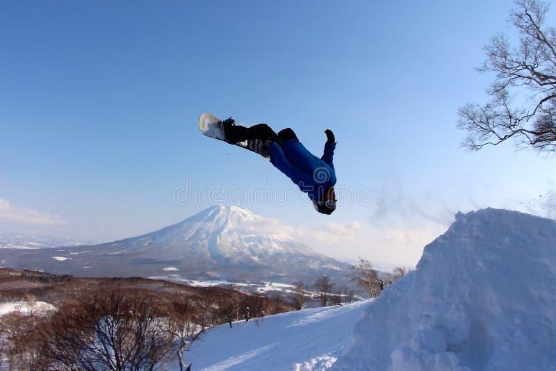 Snowboarder que envia o fora do salto backcountry imagens de stock royalty free