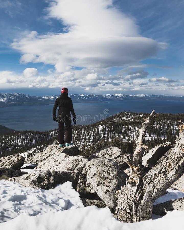 Snowboarder que está apenas na cimeira que olha para baixo em cima de Lake Tahoe e das montanhas tampadas neve fotos de stock royalty free