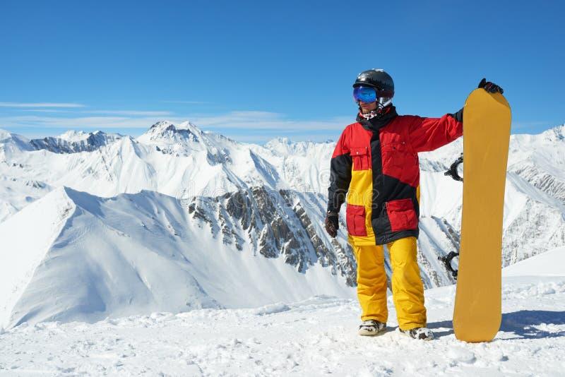 Snowboarder que está com a placa alta nas montanhas me imagem de stock royalty free