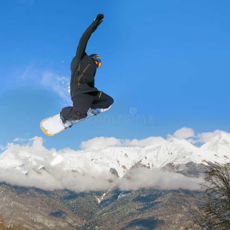 Snowboarder que hace salto de altura sobre la montaña fotografía de archivo libre de regalías