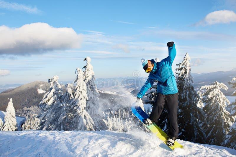 Snowboarder que hace trucos en la estación de esquí Jinete que realiza salto con su snowboard cerca de bosque en freeride backcou fotografía de archivo libre de regalías