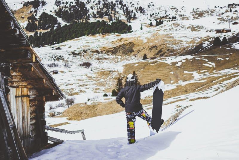 Snowboarder que lleva la chaqueta negra, máscara con la casa de madera auténtica del cierre de la snowboard Hombre que mira mount foto de archivo