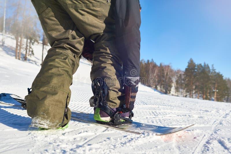 Snowboarder que põe sobre a engrenagem fotos de stock