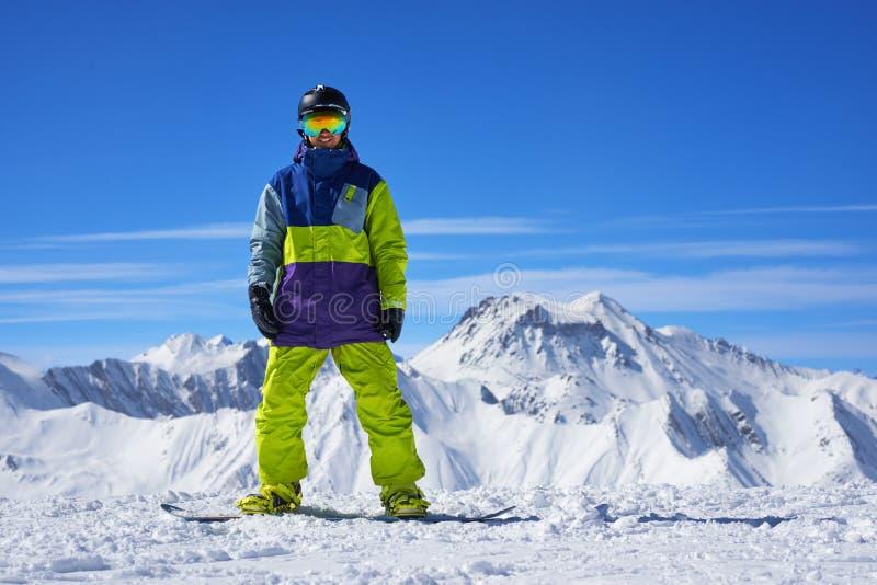 Snowboarder que se coloca en el top de una montaña foto de archivo