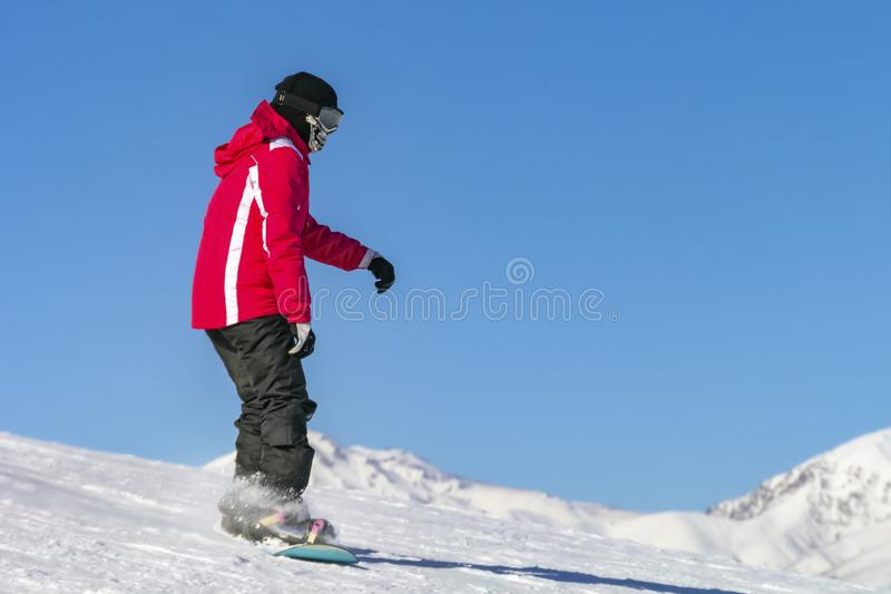 Snowboarder quickly rolls down the mountain in loose snow against a blue sky on a sunny day. stock photos