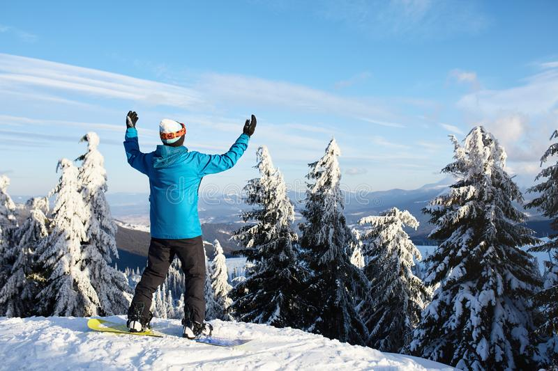 Snowboarder raised his arms and hands to the sky at ski resort. Man climbed a mountain top through forest for royalty free stock images