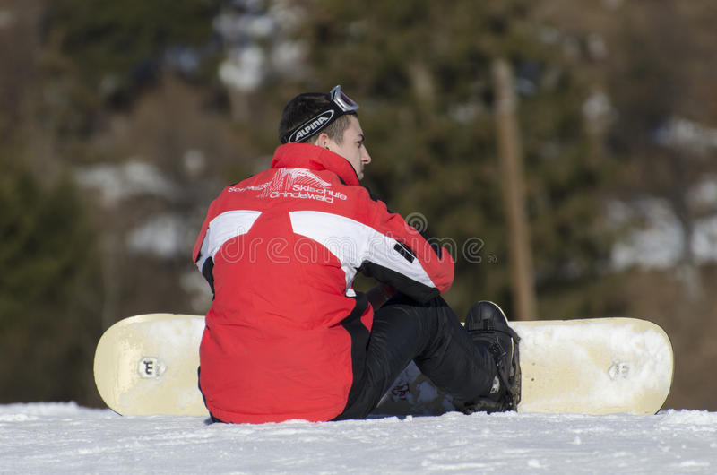 Snowboarder resting stock images
