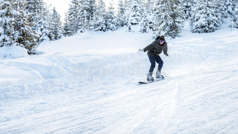 Snowboarder rides in motion on the ski slopes stock image