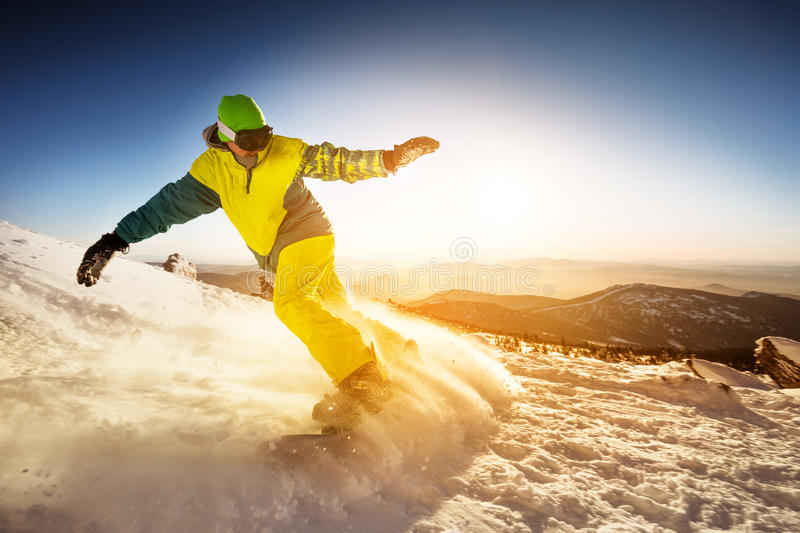 Snowboarder rides on the slope snow mountains background royalty free stock photos