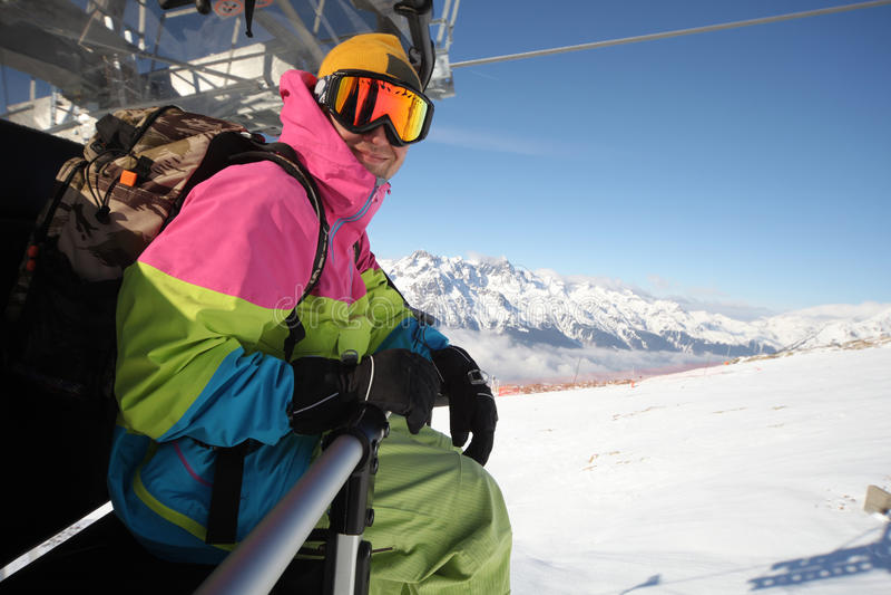 Snowboarder riding chair lift at ski resort. Caucasian man wearing goggles, riding chair lift at ski resort royalty free stock image