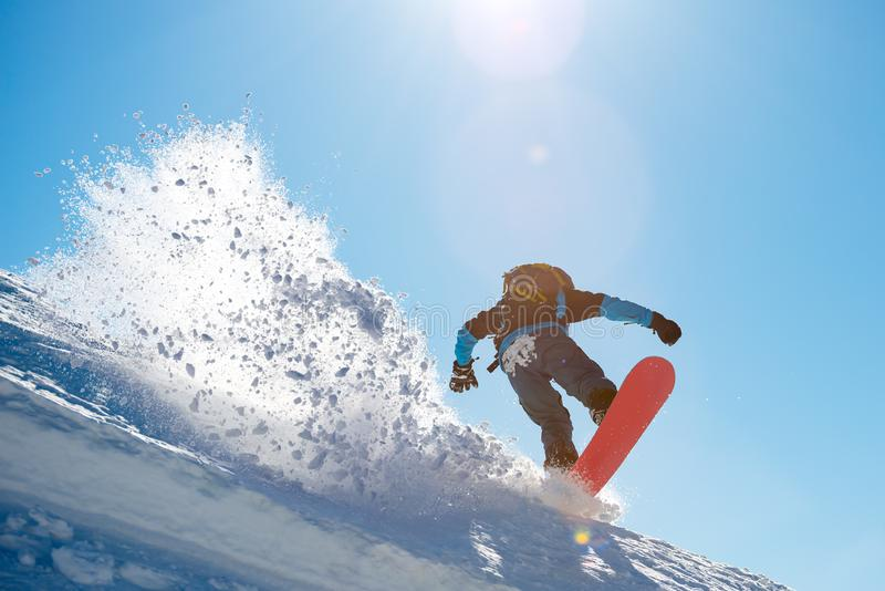 Snowboarder Riding Red Snowboard in the Mountains at Sunny Day. Big Splash of Snow. Snowboarding and Winter Sports royalty free stock image
