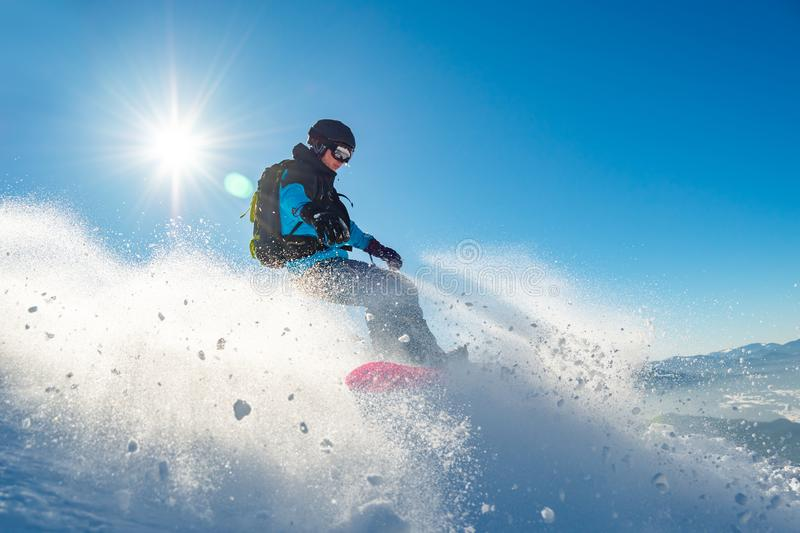 Snowboarder Riding Red Snowboard in Mountains at Sunny Day. Snowboarding and Winter Sports. Snowboarder Riding Red Snowboard in the Mountains at Sunny Day stock photo