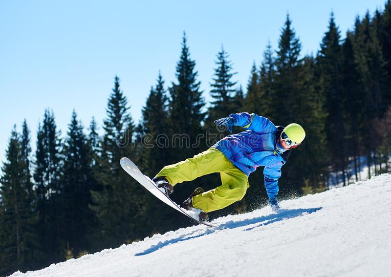 Snowboarder riding snowboard down snowy mountain slope on sunny winter day. Extreme sport concept. stock photography
