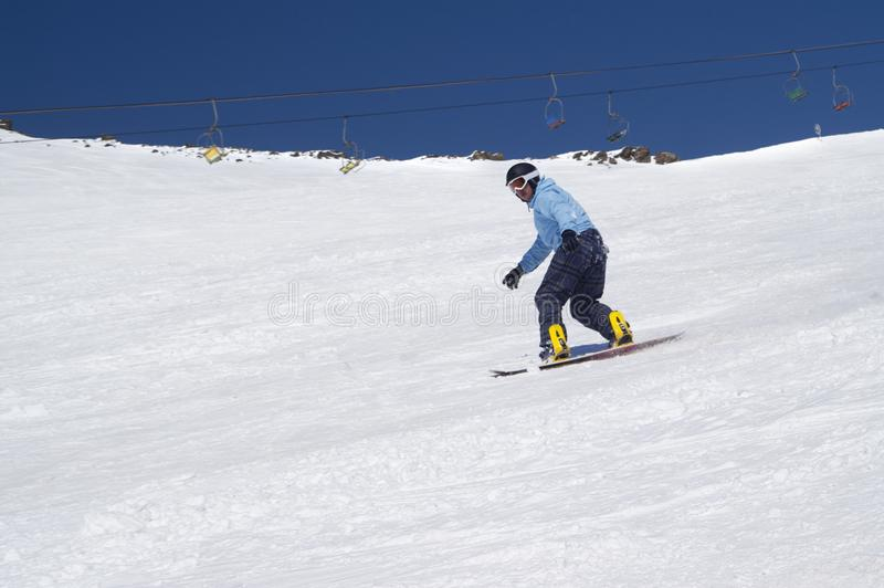 Snowboarder riding on snowy ski slope at high winter mountains in sunny day stock photography