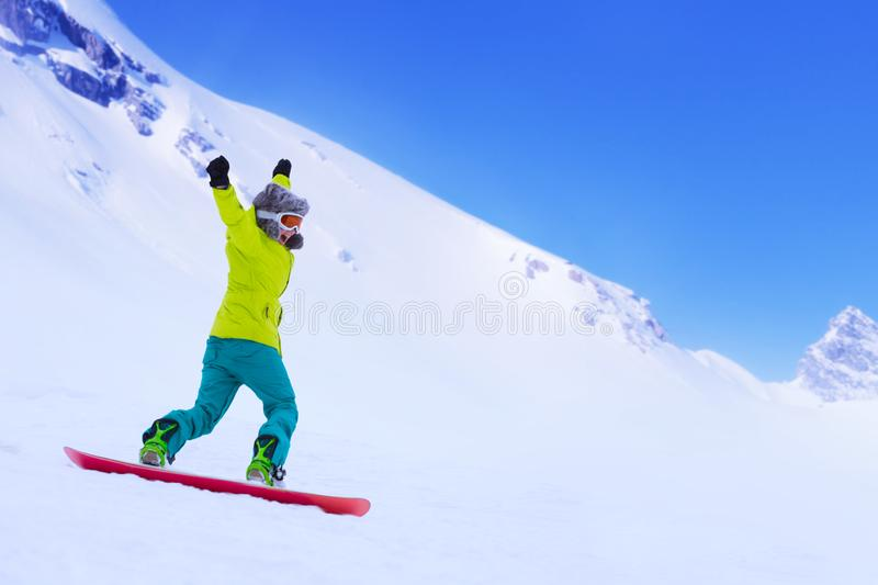 Snowboarder running down slope stock photo
