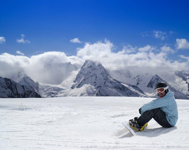 Snowboarder se reposant sur la pente de ski photographie stock