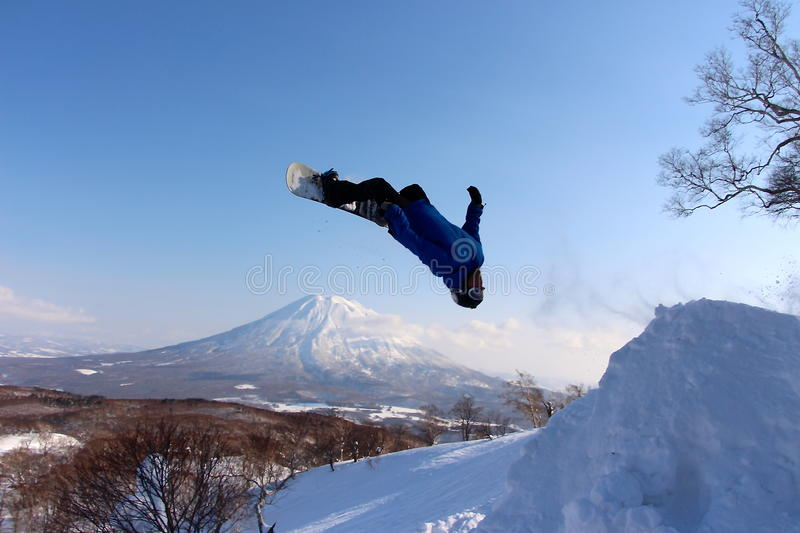 Snowboarder sending it off backcountry jump. Japan royalty free stock images